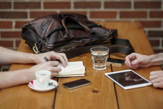 deux personnes à table avec iphone et tablette