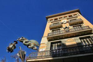 batiment de las ramblas a barcelone avec statue de dragon suspendu