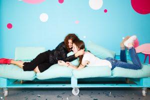 deux filles souriantes sur un canapé bleu