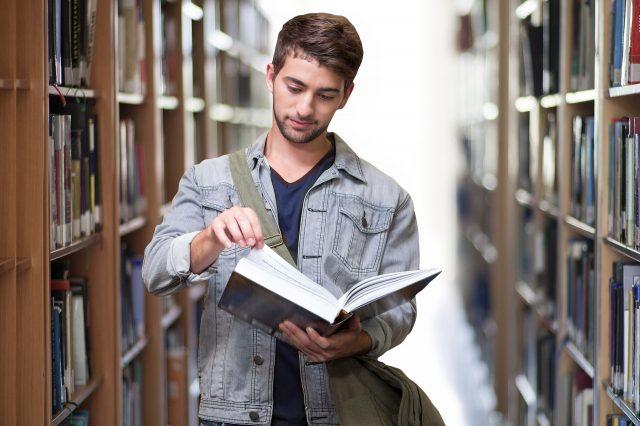 etudiant lisant un livre dans une bibliotheque