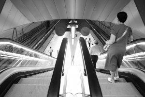 femme descendant un escalator dans un couloir