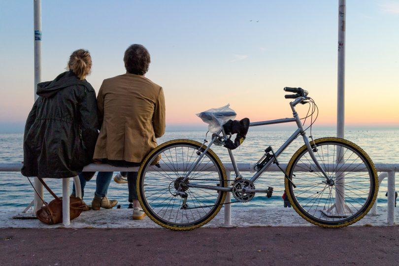 velo posé avec deux personnes face à la mer