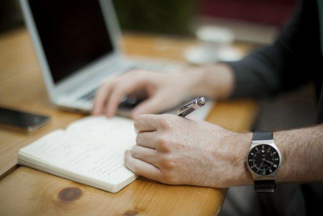 homme écrivant sur un bloc-note à côté d'un laptop