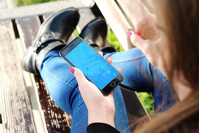 femme tenant un iphone téléphone intelligent