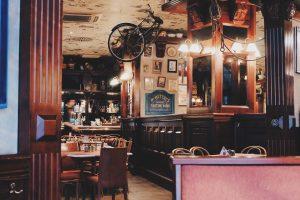 salle de bar avec tables chaises et velo suspendu