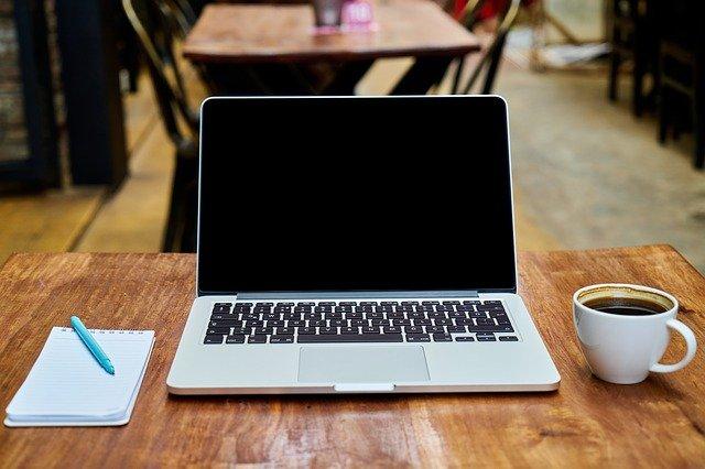 laptop sur une table avec une tasse à café et un bloc-notes