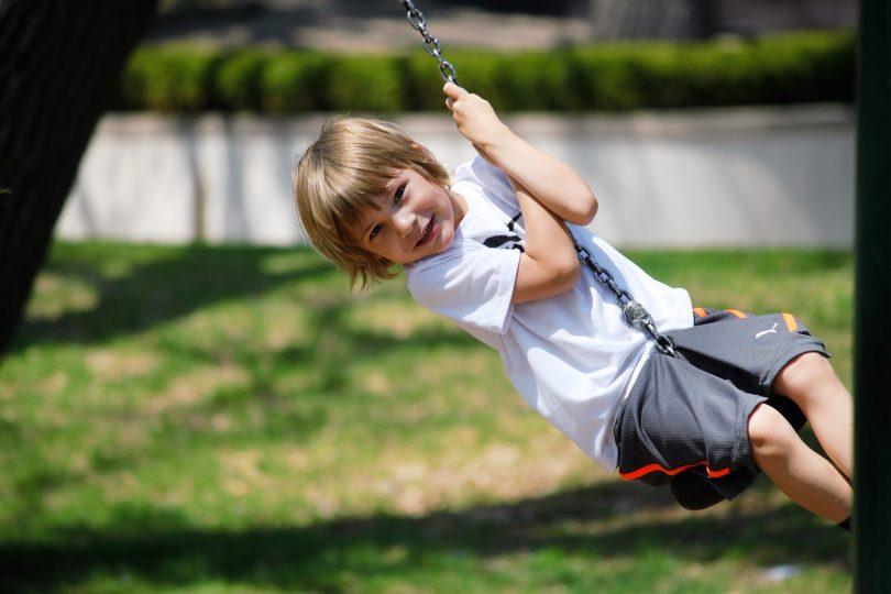 enfant blond sur balancoire