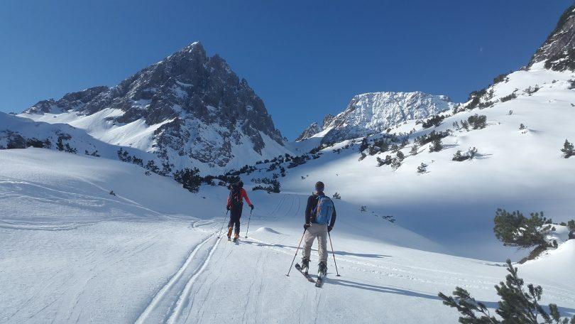 deux personnes en ski face à la montage