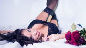 femme allongée sur un lit avec de la lingerie noire