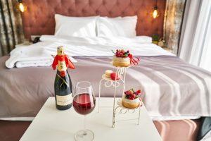 table avec verre de vin et dessert devant un lit