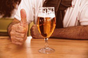 vaso de cerveza con un pulgar al lado