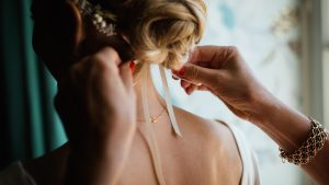 femme mettant un ruban dans les cheveux d'une mariée