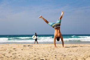 homme faisant de l'acrobatie sur la plage