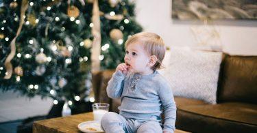 Niño comiendo sobre la mesa con árbol de navidad de fondo