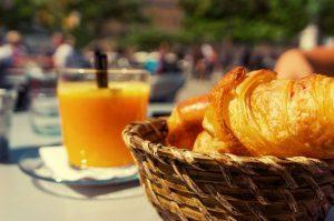 panier de croissants et verre de jus d'orange