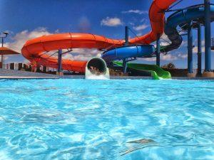 parc aquatique avec un tube orange et bleu avec piscine