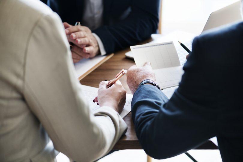 homme et femme en costume signant des papiers
