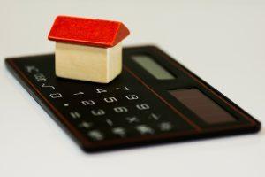 maison en bois et toit rouge sur calculatrice