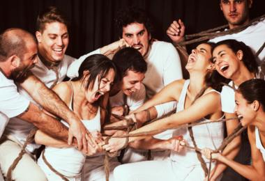 groupe mixte habillé en blanc riant et criant autour d'une corde
