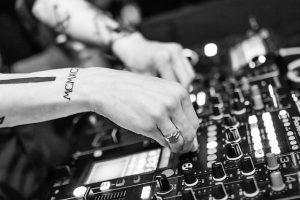 mains de dj sur une console de musique