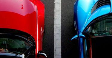 voiture rouge et voiture bleue le long d'une bande blanche