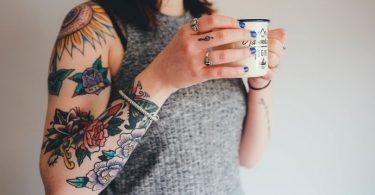 femme au bras tatoué buvant un café