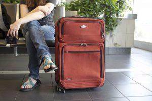 personne assise avec une valise rouge