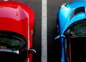 voiture rouge et voiture bleue séparées d'une ligne blanche