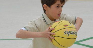 garçon en polo jouant avec un ballon de basket