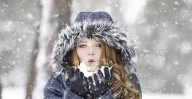 femme avec un manteau d'hiver soufflant sous la neige