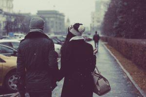 couple habillé chaudement se tenant sous la main en ville