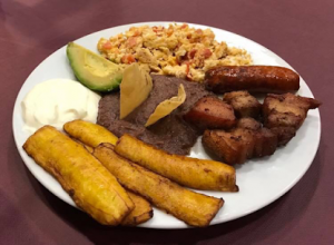 Assiette de pommes de terre, viande et riz avec morceau d'avocat.