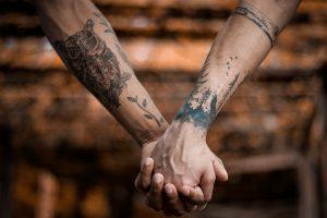 Deux personnes se tenant la main, et ayant les bras tatoués.