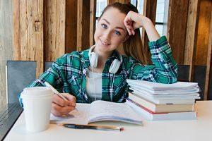 jeune étudiante écrivant avec des cahiers et des livres