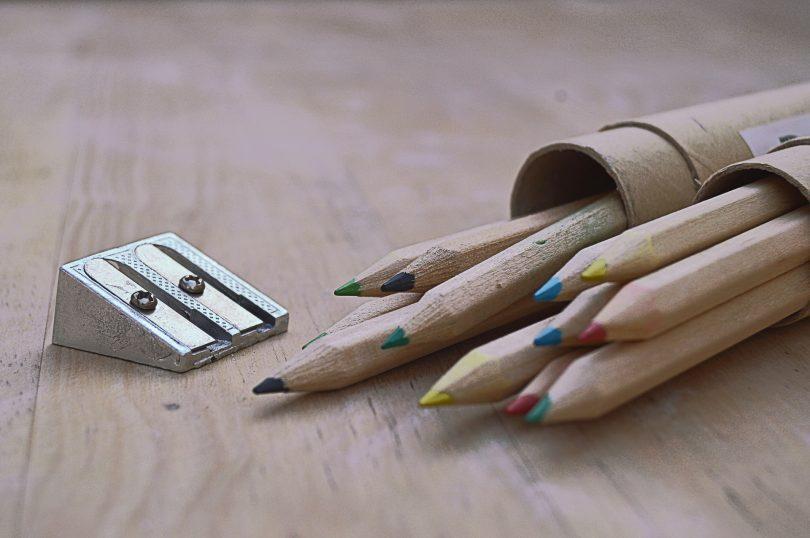 crayons de bois posés sur une table avec un taille-crayon