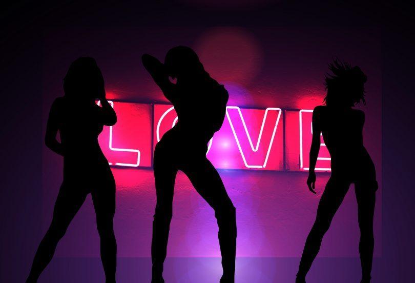 trois silhouettes de femme devant un neon rose love