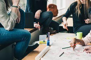 gens autour d'une table avec papier et crayons