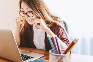 étudiante avec un crayon dans la bouche devant un ordinateur