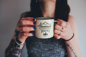 Femme tatouée tenant une tasse entre ses mains.