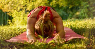 femme assise bras en avant sur une serviette dans l'herbe