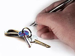 main signant avec un crayon et clés à côté