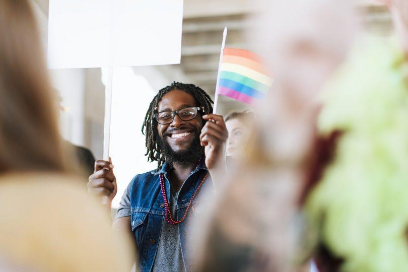 homme tenant un drapeau gay