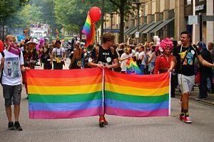 manifestation gay dans la rue avec drapeau gay