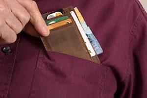 main prenant un porte-monnaie dans une poche