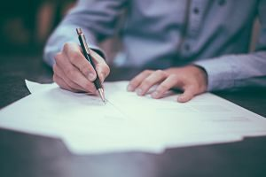 homme signant un papier