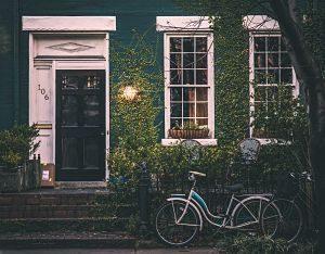 façade de maison avec du lierre et un vélo posé devant