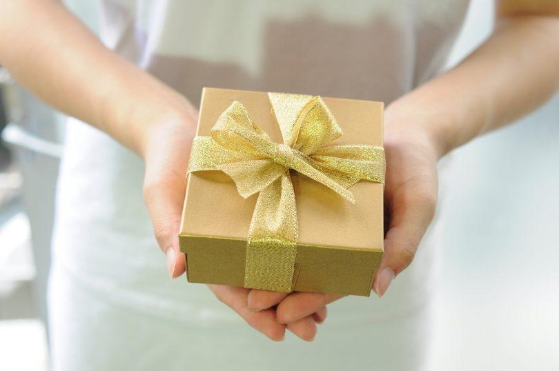 paire de mains tenant un paquet cadeau