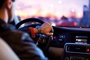 main d'un homme sur le volant d'une voiture