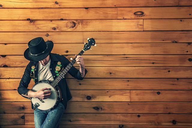 homme en chapeau jouant de la guitare