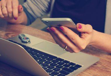 main de femme tenant un mobile devant un ordinateur